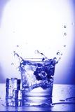 Vetro di acqua con spruzzata Fotografie Stock Libere da Diritti