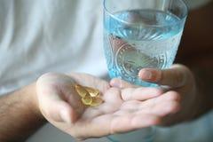 Vetro di acqua e delle pillole fotografie stock