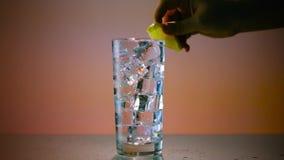 Vetro di acqua ghiacciata con il limone ampio video d archivio