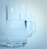 Vetro di acqua nella riga Immagine Stock