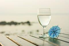 Vetro di acqua pura su una tavola scura sulla spiaggia Fotografie Stock