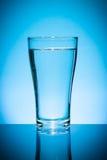 Vetro di acqua sull'azzurro Immagine Stock Libera da Diritti