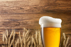 Vetro di birra con grano su legno Fotografia Stock Libera da Diritti