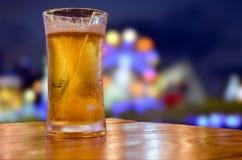 Vetro di birra con la scena della barra nei precedenti Fotografia Stock