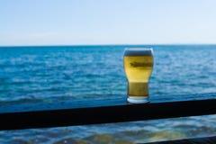 Vetro di birra contro il mare Immagini Stock