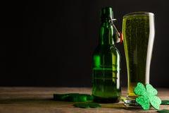 Vetro di birra, della bottiglia di birra e delle acetoselle verdi per il giorno della st Patricks Fotografia Stock