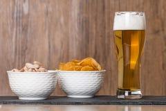 Vetro di birra, delle patatine fritte dorate e dei pistacchi in ciotola Fotografia Stock