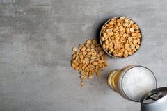 Vetro di birra e delle arachidi Immagine Stock