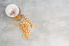 Vetro di birra e delle arachidi Fotografia Stock