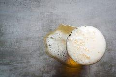 Vetro di birra e una pozza di birra sulla tavola Immagini Stock