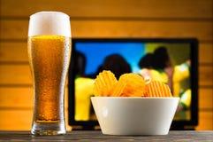 Vetro di birra fredda e delle patatine fritte Fotografie Stock Libere da Diritti