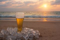 Vetro di birra fredda sulla riva di mare al tramonto Rilassi sulla spiaggia fotografie stock libere da diritti
