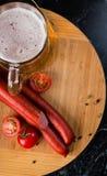 Vetro di birra leggera, delle salsiccie della carne e dei pomodori sul bordo di legno Fotografia Stock Libera da Diritti