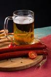 Vetro di birra leggera, delle salsiccie della carne e dei pomodori sul bordo di legno Fotografia Stock