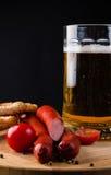 Vetro di birra leggera, delle salsiccie della carne e dei pomodori sul bordo di legno Immagine Stock