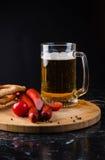 Vetro di birra leggera, delle salsiccie della carne e dei pomodori sul bordo di legno Fotografie Stock