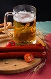 Vetro di birra leggera, delle salsiccie della carne e dei pomodori sul bordo di legno Immagini Stock Libere da Diritti