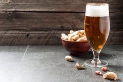 Vetro di birra schiumosa fredda leggera, dadi su un vecchio fondo di legno Immagini Stock