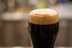 Vetro di birra scura immagine stock