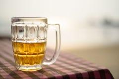 Vetro di birra su una tavola sui precedenti del mare fotografia stock