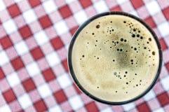 Vetro di birra sul fondo d'annata rosso e bianco della tovaglia Immagini Stock Libere da Diritti