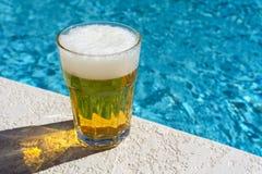 Vetro di birra sul patio concreto e sul fondo confuso della piscina fotografie stock