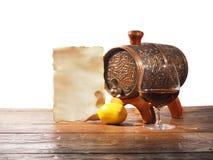 Vetro di brandy, barilotto, vecchia carta su un fondo bianco Fotografia Stock Libera da Diritti