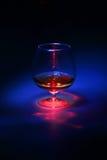 Vetro di brandy con luce astratta e blu rossa Immagine Stock