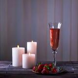 Vetro di champagne e delle fragole rosa su una tavola di legno Fotografie Stock