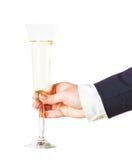 Vetro di champagne scintillante in una mano femminile Fotografie Stock Libere da Diritti