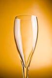 Vetro di Champagne su una priorità bassa dorata Immagini Stock Libere da Diritti
