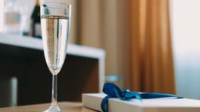 Vetro di champagne sulla tavola Bokeh, bolle in un vetro di champagne stock footage