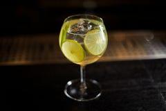 Vetro di cocktail elegante con il cocktail acido e dolce fresco dell'agrume nel fondo scuro immagini stock libere da diritti