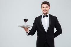 Vetro di condizione e della tenuta del cameriere di vino rosso sul vassoio immagine stock