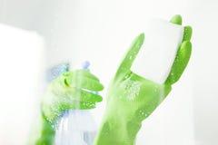 Vetro di finestra di pulizia con il detersivo immagine stock