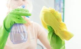 Vetro di finestra di pulizia con il detersivo Fotografia Stock