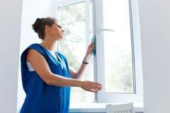 Vetro di finestra di pulizia della giovane donna Lavoratore di Cleaning Company Fotografie Stock