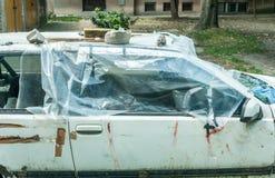 Vetro di finestra rotto e rotto sulle porte di automobile nocive coperte di fine di plastica del nylon su dopo l'incidente di arr immagini stock libere da diritti