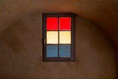 Vetro di finestra variopinto in giallo rosso e blu mascherati in cantina Immagini Stock