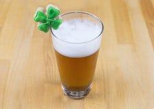 Vetro di giorno di Patrick di birra e dei biscotti non filtrati leggeri con il trifoglio verde Immagine Stock