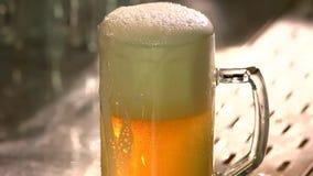 Vetro di gocciolamento riempito troppo di birra sulla tavola della barra video d archivio