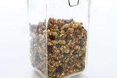 Vetro di granola al forno domestico su bianco Fotografia Stock
