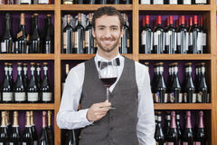 Vetro di Holding Red Wine del barista contro gli scaffali Fotografia Stock