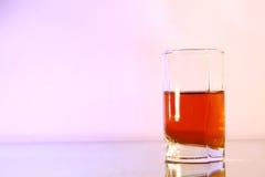 Vetro di liquore sul fondo marrone di pendenza Fotografia Stock