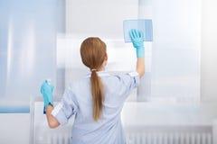 Vetro di pulizia della domestica felice Fotografia Stock