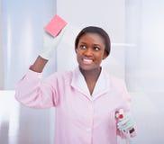 Vetro di pulizia della governante femminile in hotel immagine stock libera da diritti