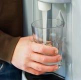 Vetro di riempimento con acqua dall'erogatore Fotografie Stock Libere da Diritti