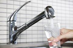 Vetro di riempimento di acque di rubinetto fotografie stock