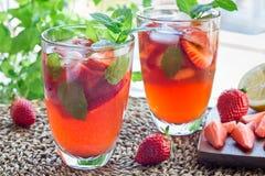 Vetro di rinfresco del tè ghiacciato con le fragole e la menta, orizzonte immagini stock