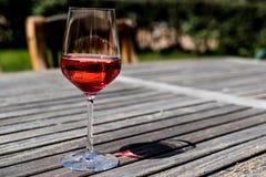 Vetro di Rose Wine alla luce naturale del giardino Immagine Stock
